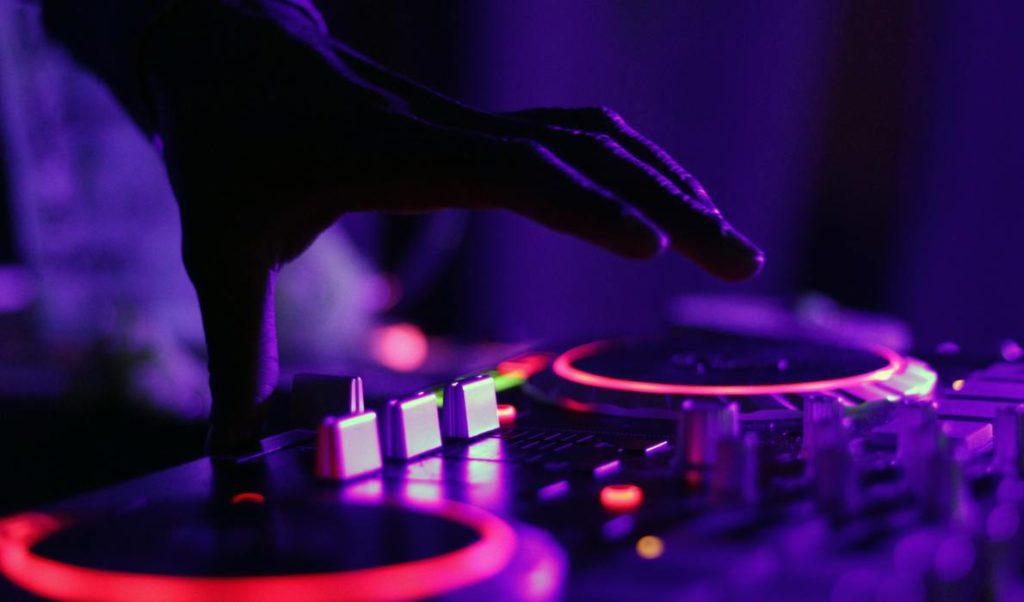 Hånd som spiller på opplyst dj sett