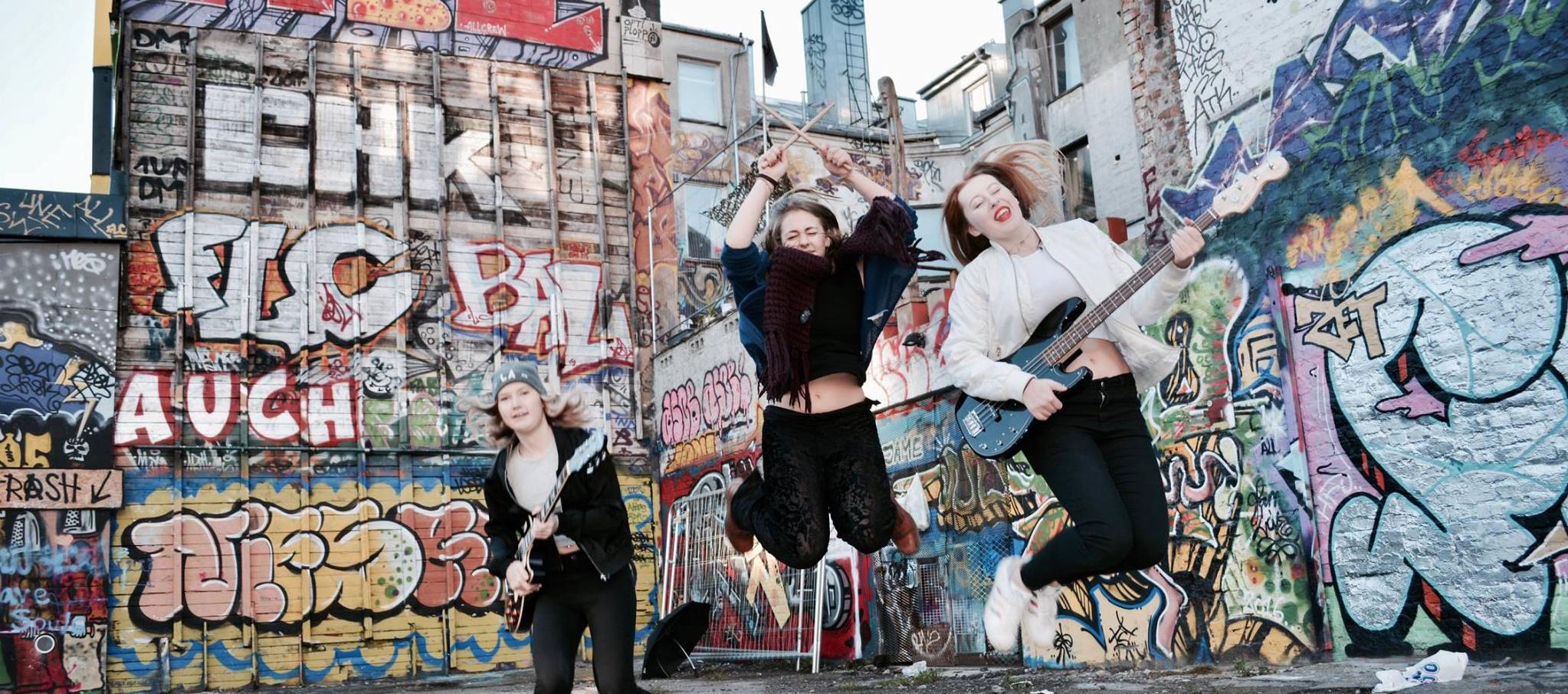 Tre jenter med bandinstrumenter som hopper. Veggene bak er dekket av grafitti.
