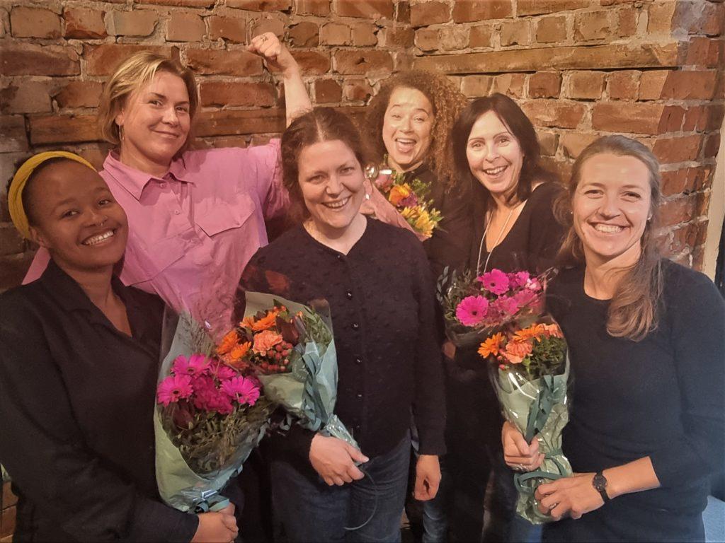 Seks kvinner smiler med blomsterbuketter i hendene